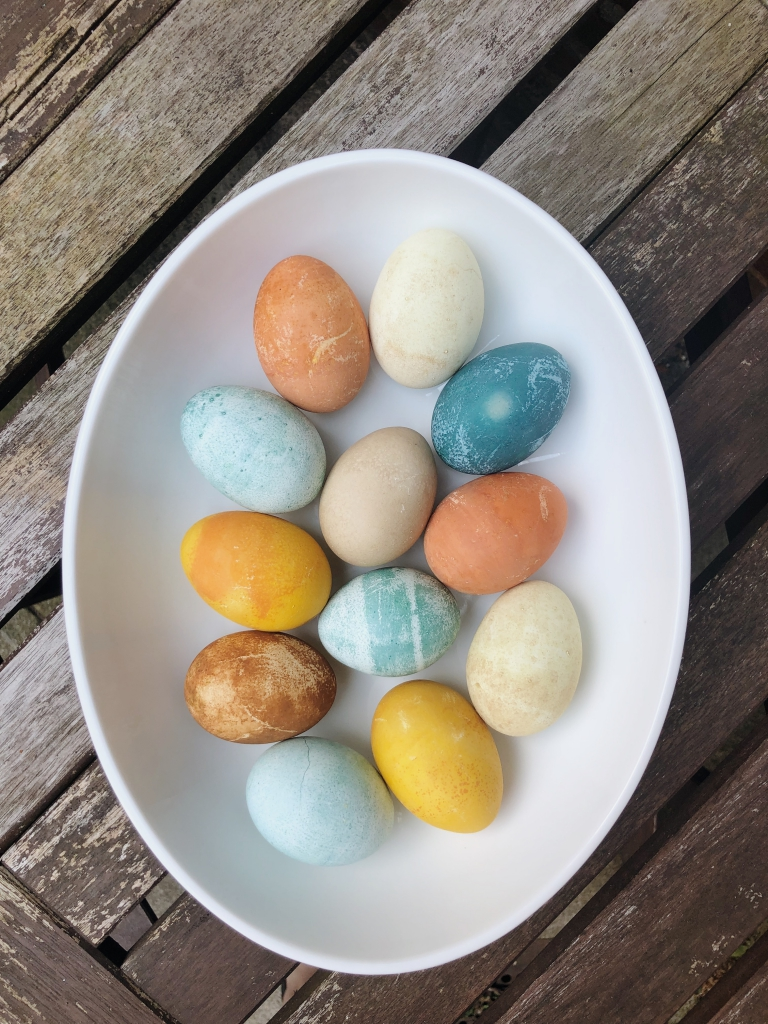 Naturally colored Easter eggs from vegetable dyes sitting in an oval bowl on a table