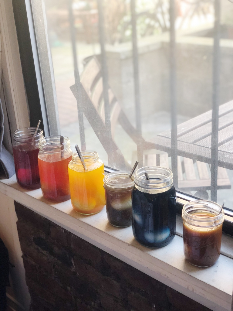 Glass jars of natural Easter egg dye sitting on a windowsill